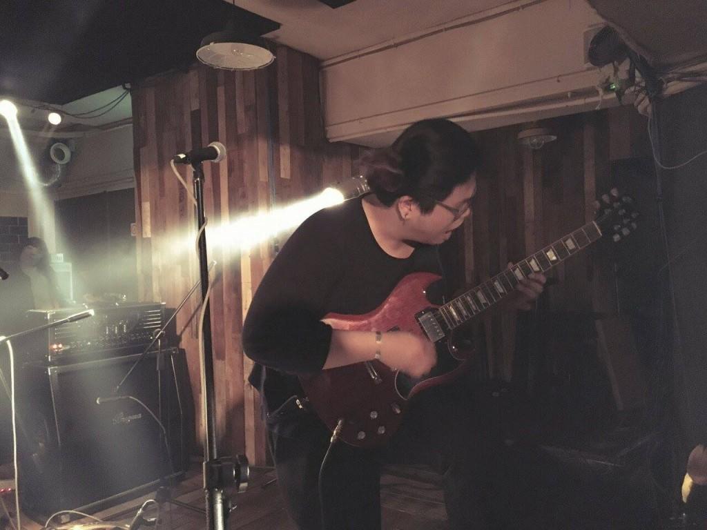 体慾股長吉他手昱誠拿著粗大 Band 主唱老盧的 SG