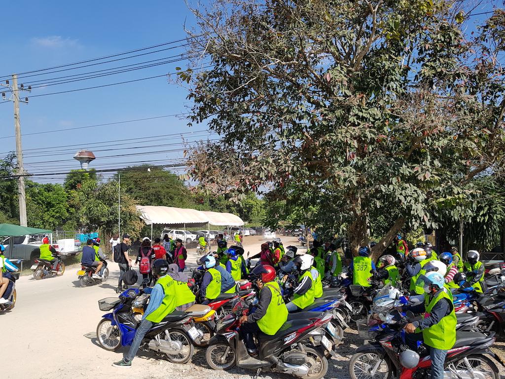 在公路旁伺機等待的接駁摩托車隊,穿著官方認證的綠色背心。