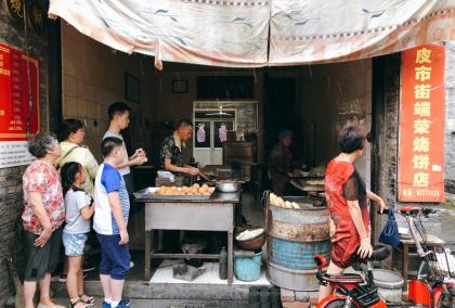 在皮市街的一家燒餅店,我們買一些糍粑給他們吃,走到店裡時又下起雨來。